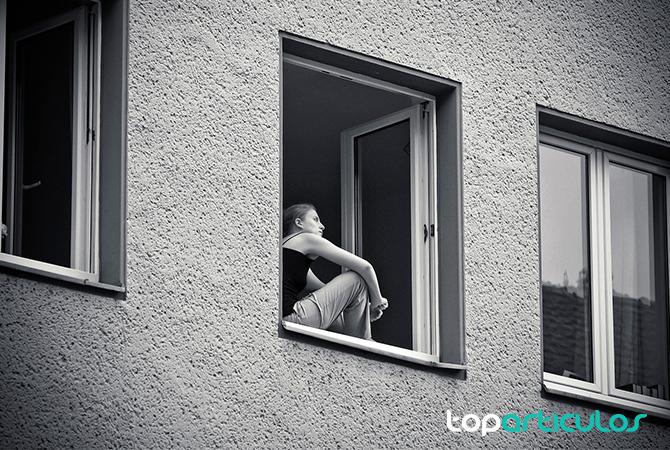 Mujer pensativa en su vivienda.