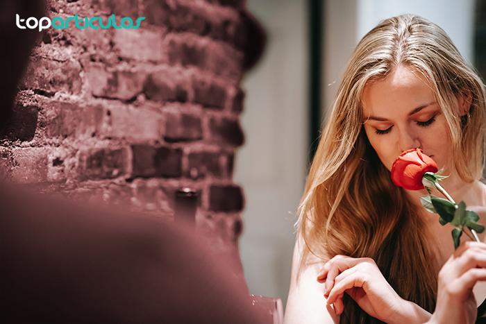 Chica recibiendo una rosa de su cita que consiguió después de ligar por internet