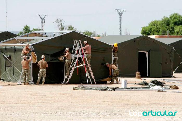 Grupo de militares instalando tiendas de campaña móviles de ayuda humanitaria.