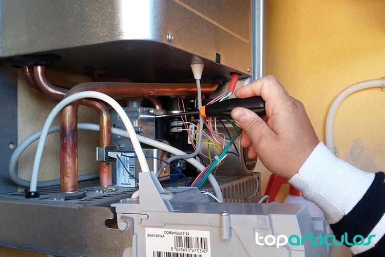 Vista de un técnico haciendo el mantenimiento a una caldera